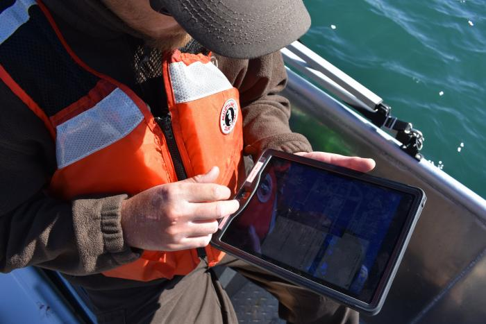 Biologist in a boat working on a tablet computer